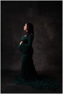 In studio maternity photography photo of pregnant mom in a dark green gown.