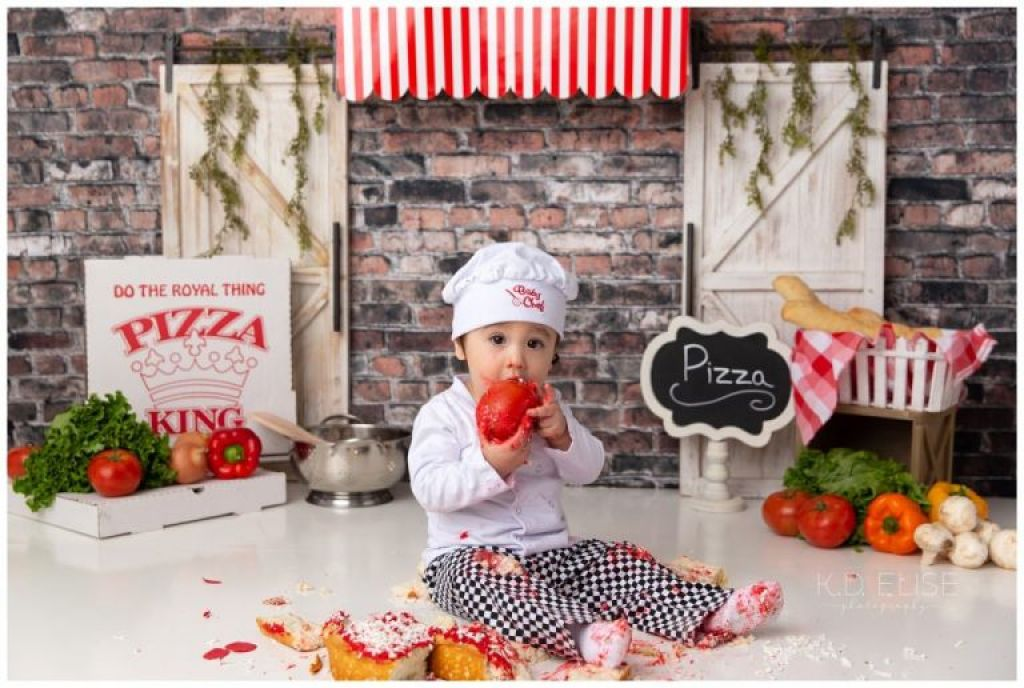 Pizza themed cake smash photo of a baby boy in a chef costume, eating a tomato. He is sitting beside a pile of broken up cake. The backdrop is brick, with a red and white striped awning and a white wooden door on either side.