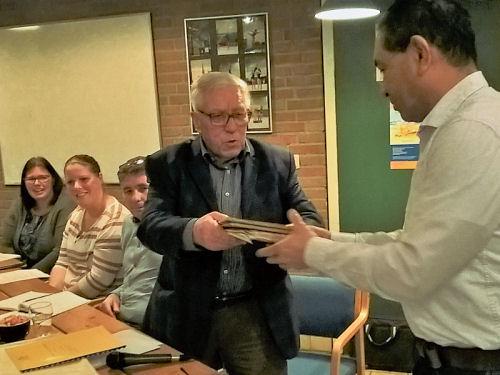 Piet draagt de notulen (met de hand geschreven boeken) over aan onze nieuwe voorzitter Willem...