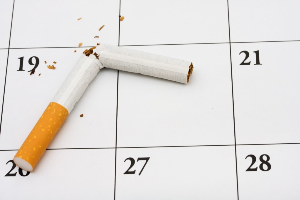 A broken cigarette lying on a calendar symbolising quitting smoking this month.