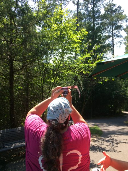 Animal Department Director uses her cell phone and eclipse glasses to take a photo of the eclipse
