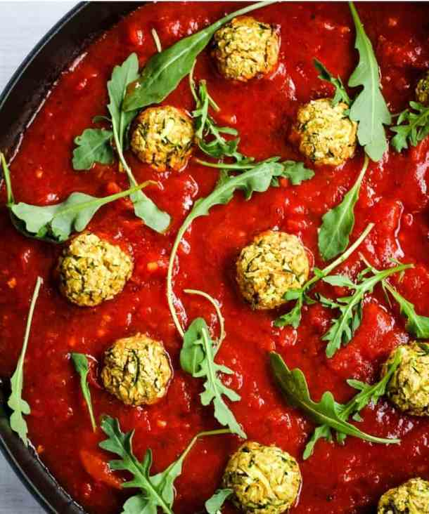 chickpea meatballs in saucepan with marinara sauce and arugula