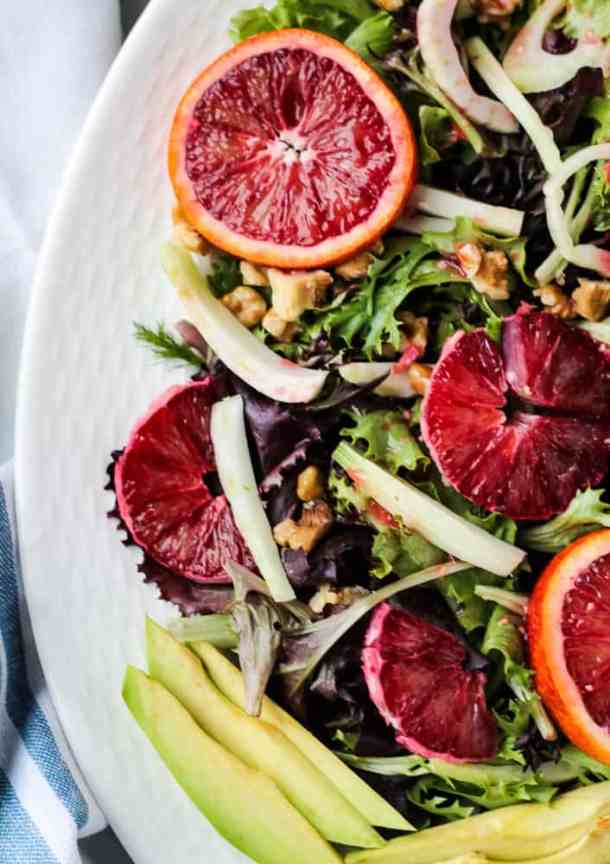 close up of blood oranges on a bed of greens
