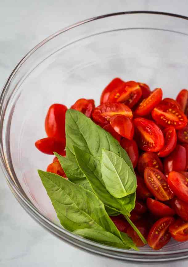 cherry tomatoes and basil in glass bowl