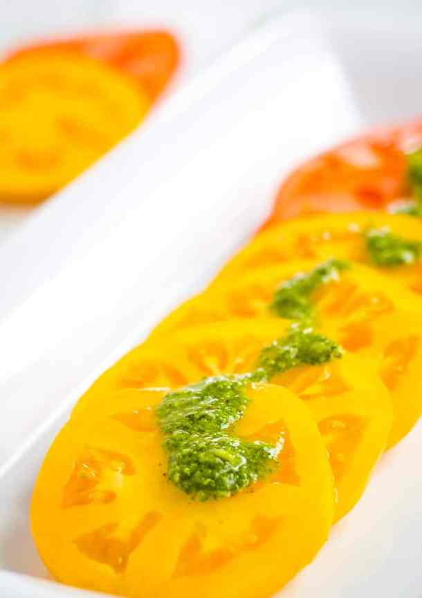 sliced tomato with basil sauce overtop