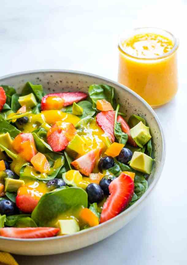 berry salad in gray bowl with mango dressing in background