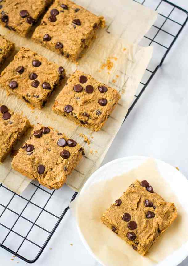 blondies on cooling rack next to a blondie on a white plate