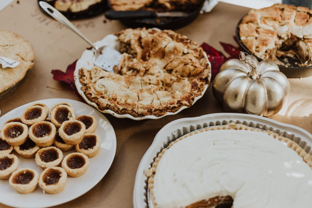 Hosting Thanksgiving: Table with apple pie, gold pumpkin Thanksgiving decoration and a few other Thanksgiving desserts