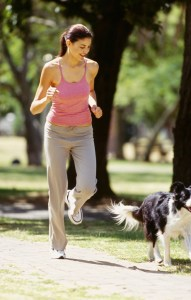 young woman jogging with her dog in a park