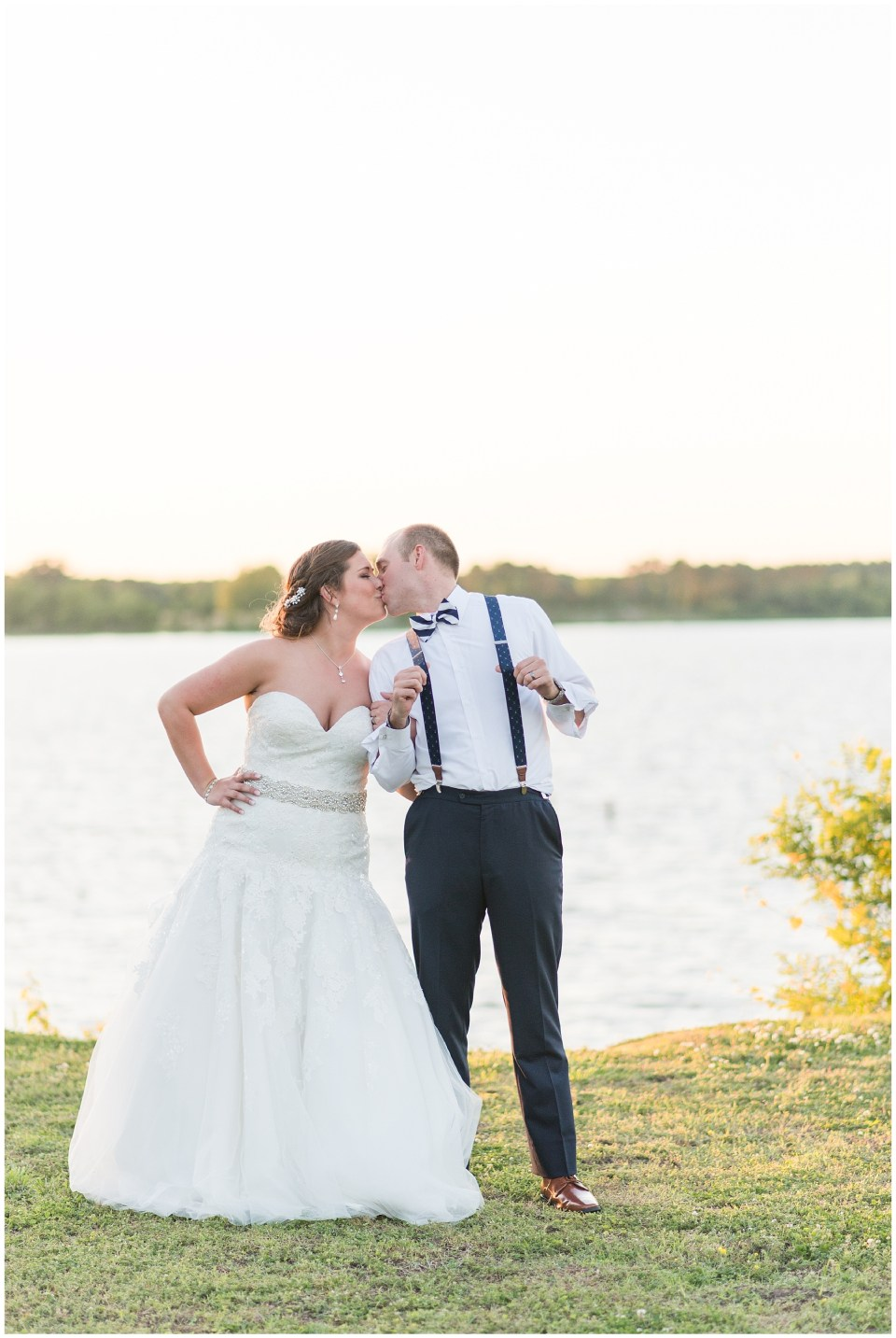 bride and groom kissing by water
