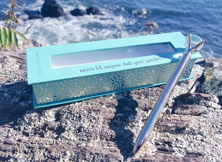 diamond and gold pen with its box on a bed of beach rock