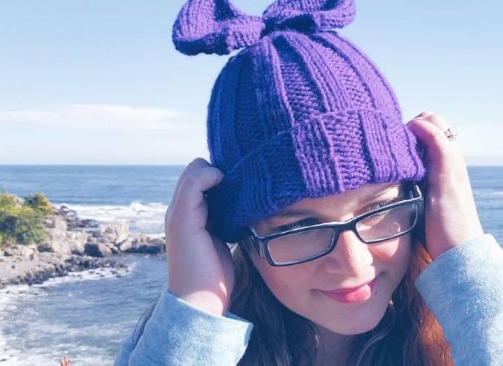 purple bow knit hat with sea in the background