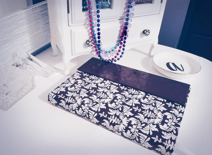 purple and white journal lying on top of a vanity with jewelry box an a plate in background