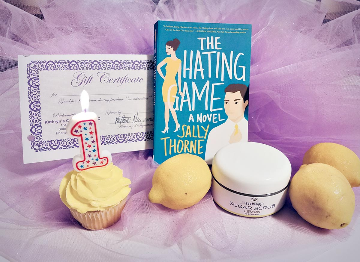 a lemon cupcake. 3 lemons, the hating game book and a kathryns confections gift certificate on purple sparkly background