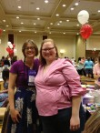 Jennifer Lohmann and Kelly Maher at the 2014 RT Booklovers Convention book signing. Jennifer is wearing a purple short-sleeved top with a blue skirt with a white floral print, and Kelly is wearing a pink wrap shirt with capri jeans.