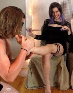 female dominant kelly sunshine receiving foot massage from male slave