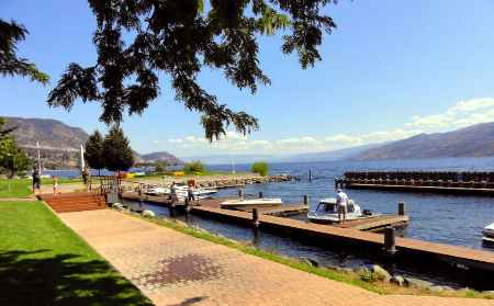 Peachland boat parking with several boats moored and summer time view of the waterfront walkway.