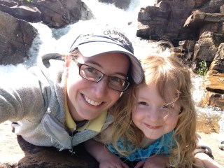 Kelsey and Rayleigh on a rock in the middle of the waterfall.