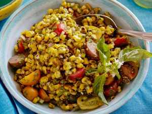 corn salad with cherry tomatoes and herbs in a bowl