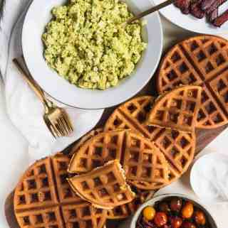 a stack of savory waffles next to a bowl of avocado scrambled eggs and