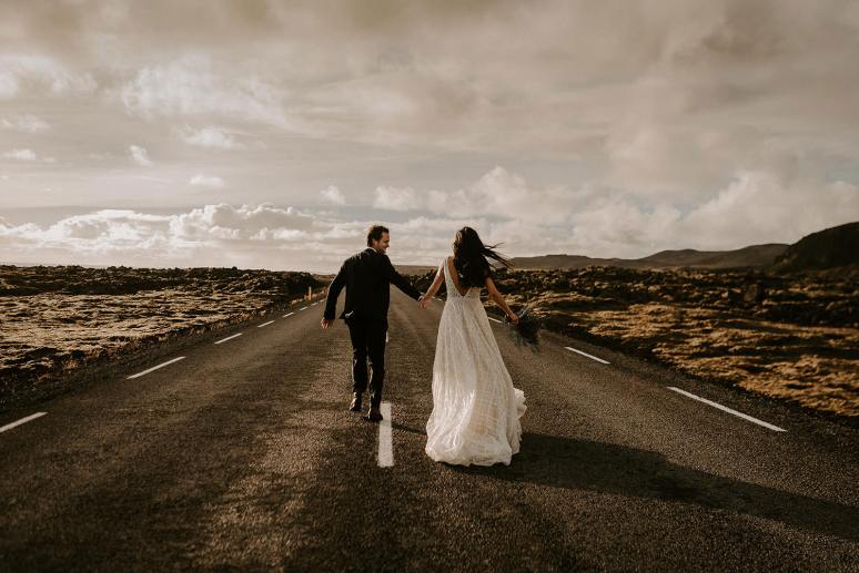 Bride and groom running along the road together during their Iceland elopement