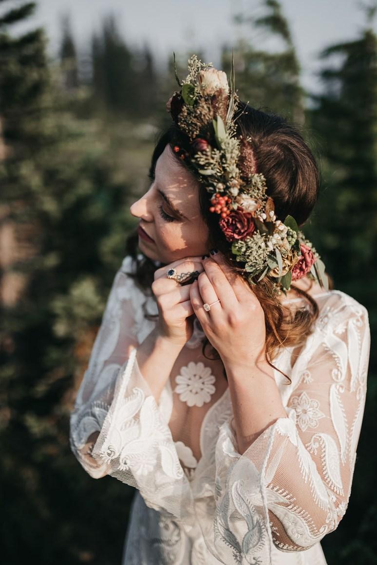 moonlight magic rue de seine wedding dress worn by bride as she puts on her earrings wearing a flower crown