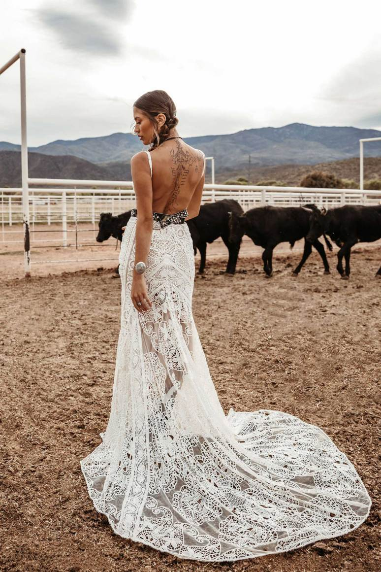 gorgeous backless lace wedding dress worn by bohemian bride with cows in the background