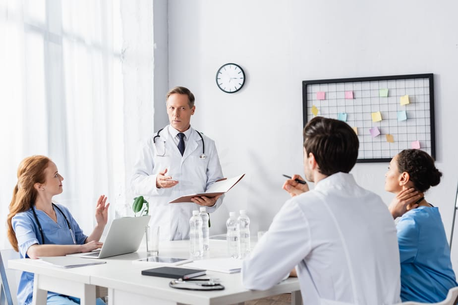 A group of four healthcare workers gathers in a conference room, reviewing notes on laptops and clipboards while having a discussion.