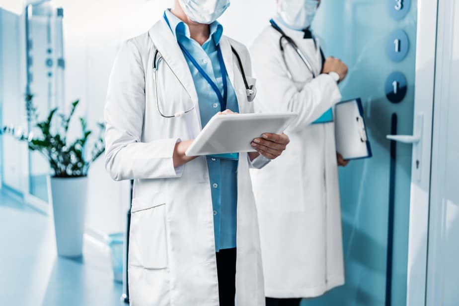 Two doctors in white coats with stethoscopes around their necks carry clipboards and wear surgical masks.