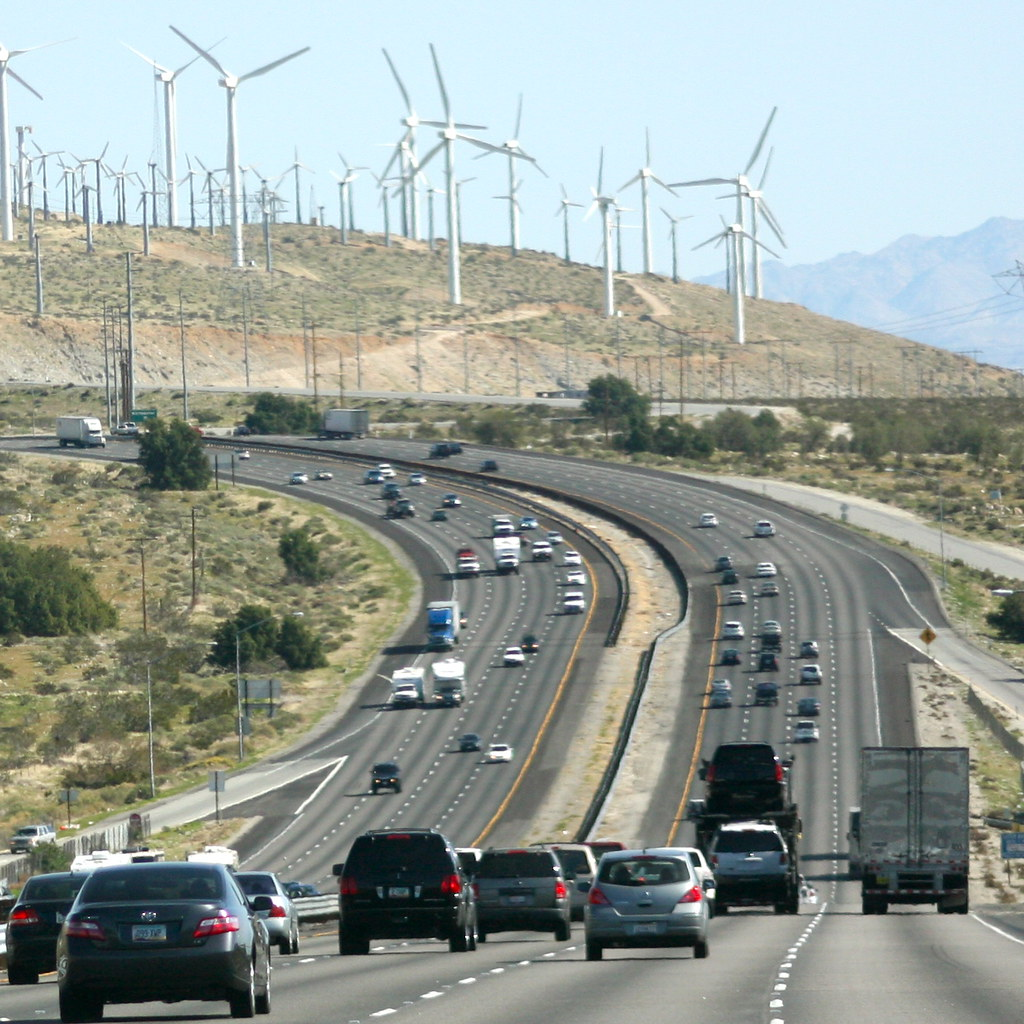 Cars on freeway in foreground, wind turbines in distance