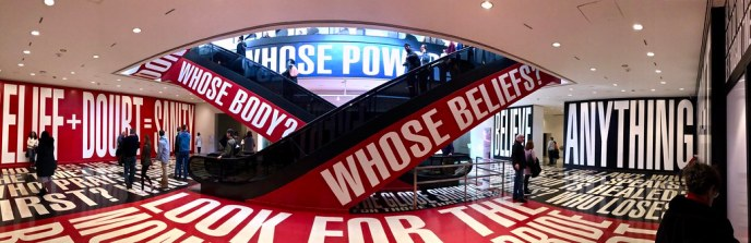 """Escalators in museum surrounded by display with large words: """"Belief + Doubt = Sanity"""", """"Believe Anything"""", """"Whose Body?"""" """"Whose Beliefs?"""""""