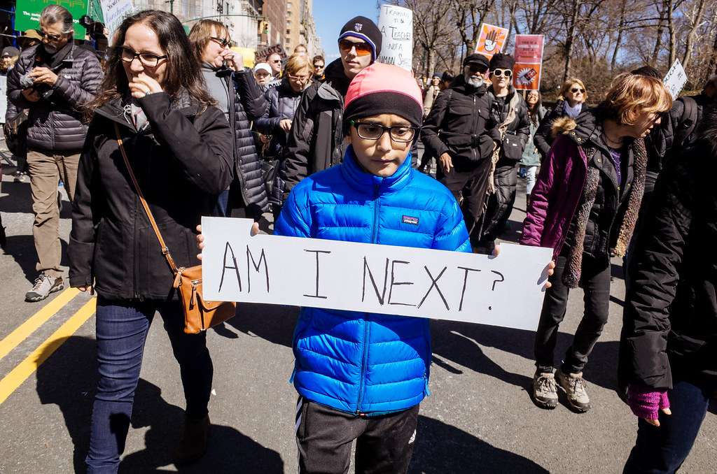 "Teenager leading marchers, carrying sign reading, ""Am I Next?"""