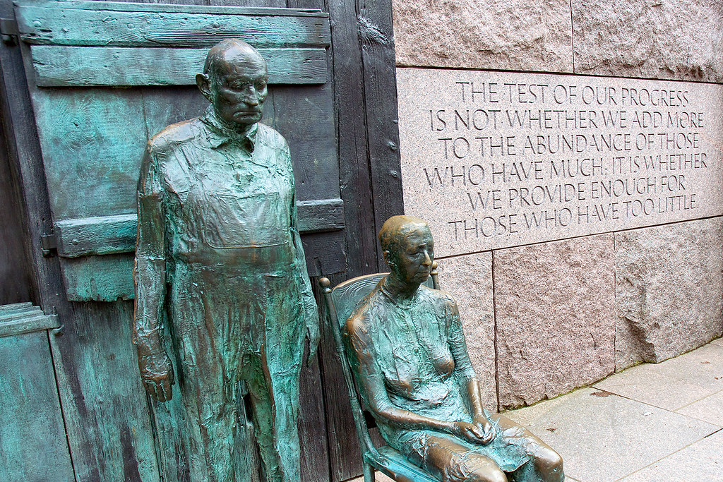 """Statues of depression-era farming couple with FDR quote: """"The test of our progress is not whether we add more to the abundance of those who have much; it is whether we provide enough for those who have too little."""""""