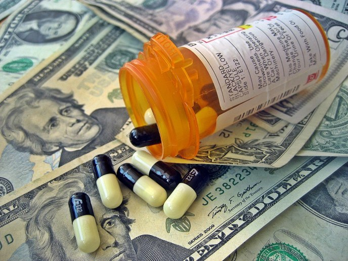A pill bottle spills capsules out onto a pile of money
