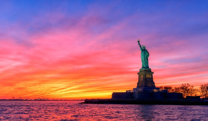 The Statue of Liberty silhouetted against a colorful sunset
