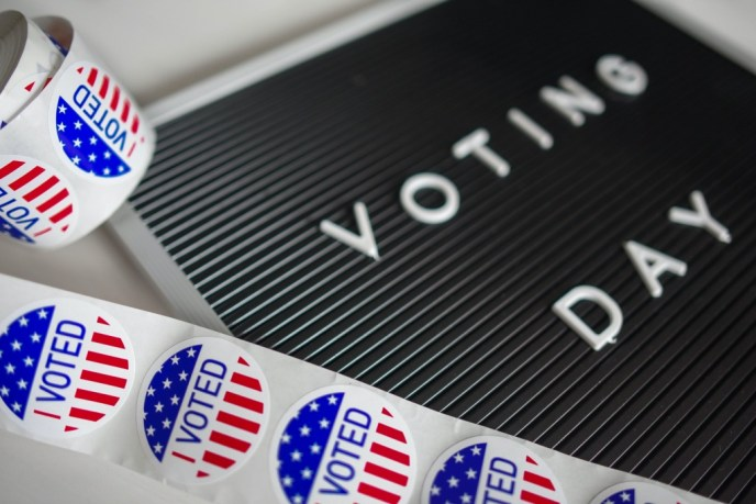 """""""I Voted"""" stickers with a signboard reading """"Voting Day"""""""