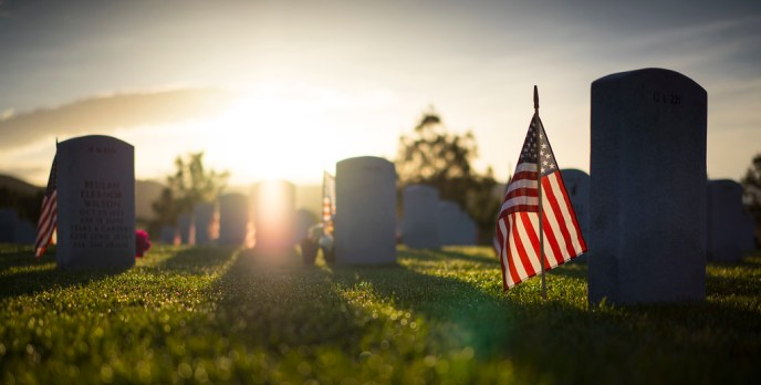 Dawn breaks over a veterans cemetery with American flags planted at each headstone