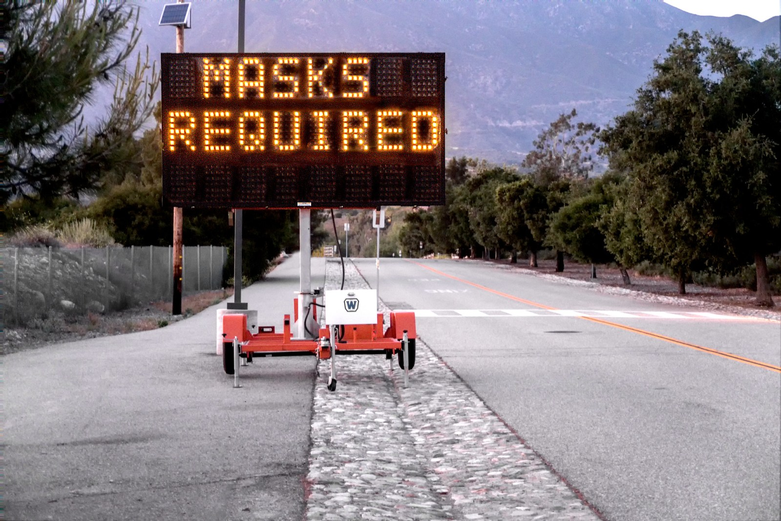 "The message ""Masks Required"" on a digital roadway sign."