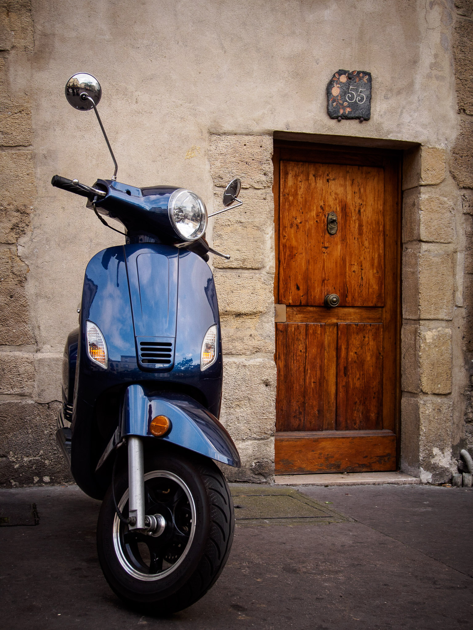 Blue scooter in front of an old wooden door in Paris, France Olympus OMD E-M5, 1/80 sec, ƒ6.3, 25mm (50mm full-frame equivalent), ISO320