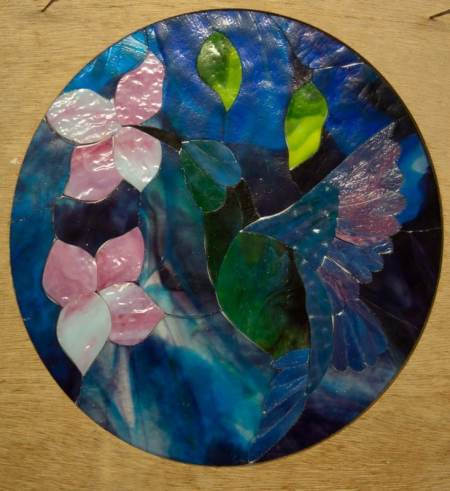 Hummingbird with Blossoms round stained glass panel, all the pieces cut, pink blossoms with blue and purple background.