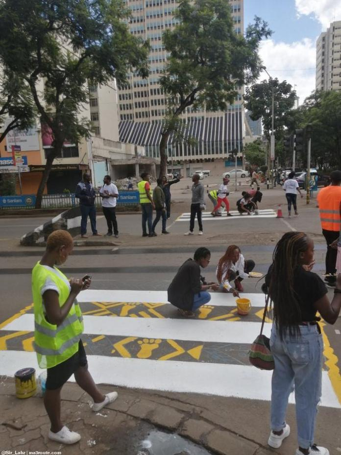 Creatives painting graffiti on a road in Nairobi CBD