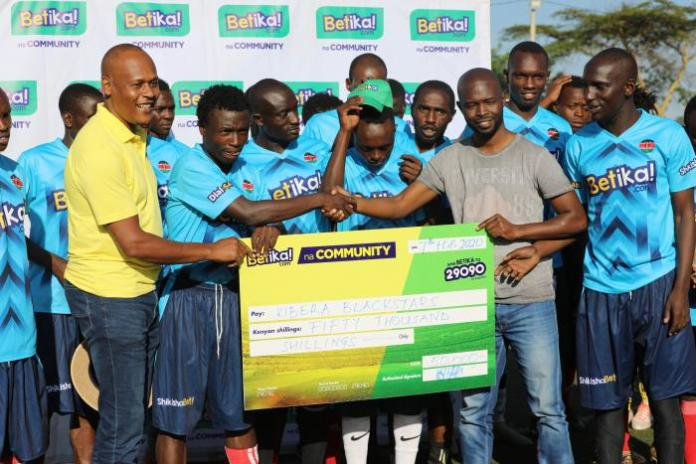 Betika's Head of Commercial John Mbatiah (left) when he presented Kibera Blackstars with a cheque for Ksh 50,000 at the Camp Toyoyo grounds on Friday, February 7, 2020.