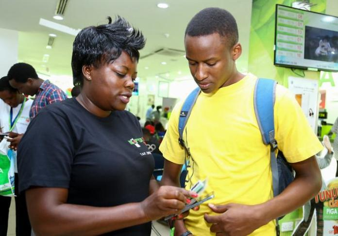 Photo of a Safaricom agent demonstrating how to sign upfor post pay plan