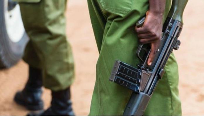 A Kenyan police officer holding a gun