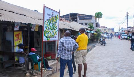 Residents look at one of the vandalized billboards pictured in Nyali, Mombasa on August 16, 2020