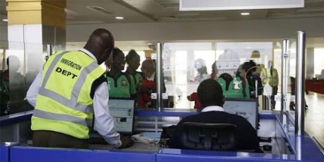 A photo of an immigration official serves travellers at the Jomo Kenyatta International Airport (JKIA) in Nairobi.