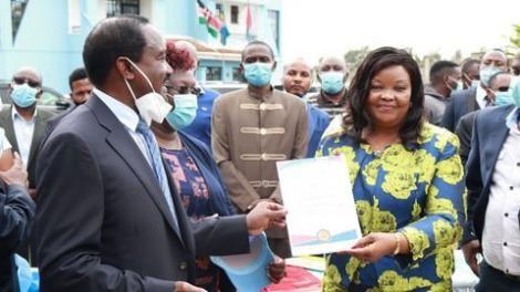 Wiper Kenya Party Leader Kalonzo Musyoka presents Agnes Kavindu with her nomination cetificate.