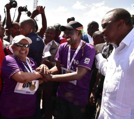 First Lady Margaret Kenyatta (left) is congratulated by Deputy President William Ruto (centre) after completing her 10km race as President Kenyatta looks on at the Beyond Zero Marathon in 2019.