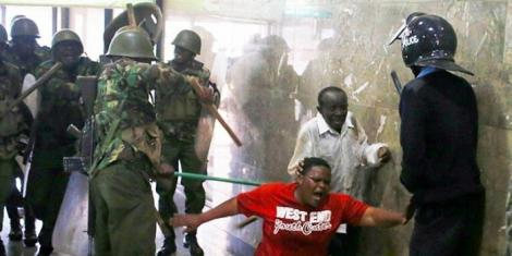 Police assault a Kenyans on March 27, 2020, as the nationwide curfew commenced