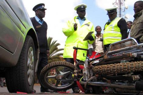 Police officers at an accident scene involving a car and a motorbike in Nyeri County on July 11, 2011.
